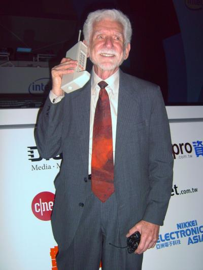 Martin Cooper holding a prototype handheld phone